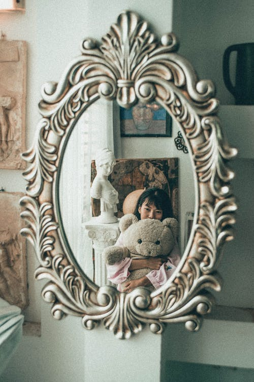 Mirror in elegant massive frame reflecting charming young Asian female cuddling with fluffy bear toy in light bedroom