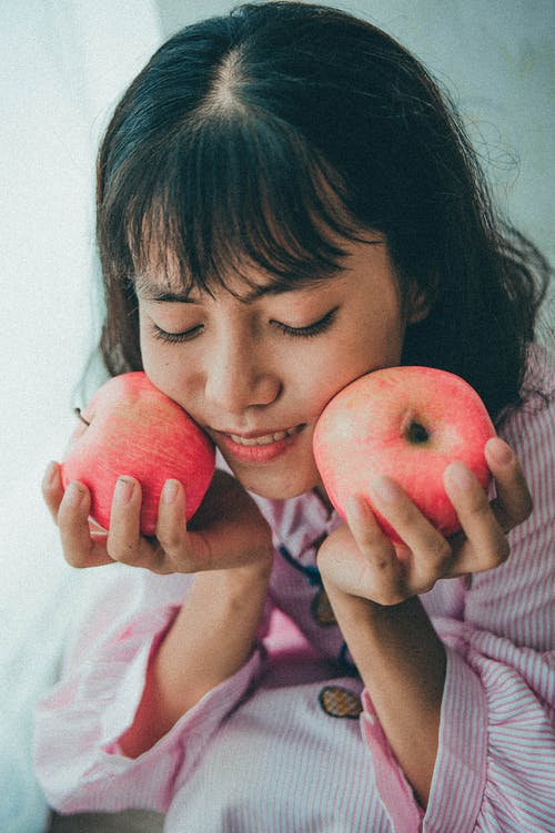Woman in Pink and White Stripe Shirt Holding Two Apples
