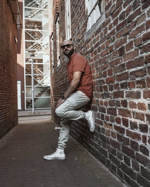 Man in Brown Polo Shirt and White Pants Leaning on Brown Brick Wall