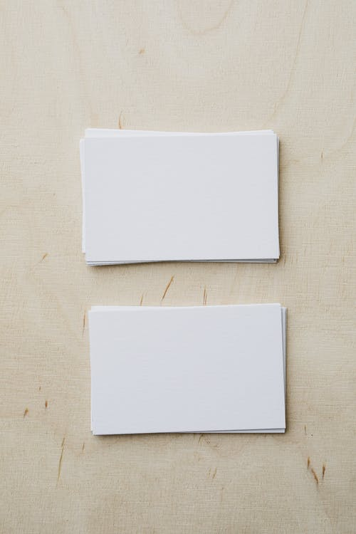 Top view of stacks of white mockup greeting cards placed on light wooden desk in soft daylight