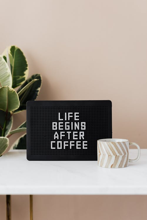 Light up letter message board reading Life Begins After Coffee and ceramic coffee cup on table with green pot plant near pastel pink wall