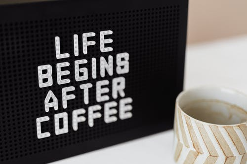 Peg message board with Life Begins After Coffee motto and empty ceramic cup of coffee with creative striped design on white table