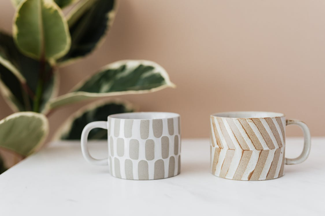 Handmade ceramic mugs with creative designs placed on white marble table with blurred green house plant near pink wall in background