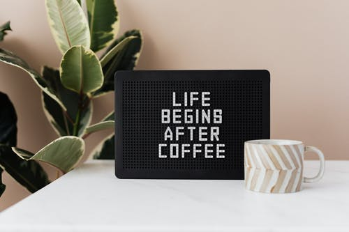 Message board with funny motto and cup of coffee
