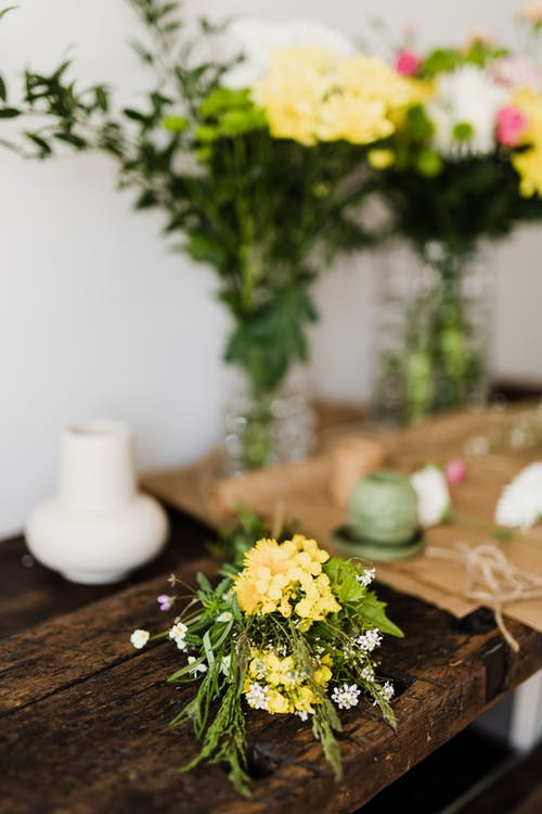 Fresh bouquet placed on wooden table for pruning