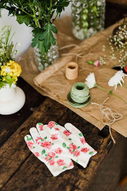 Florist gloves on table with bouquets and twine