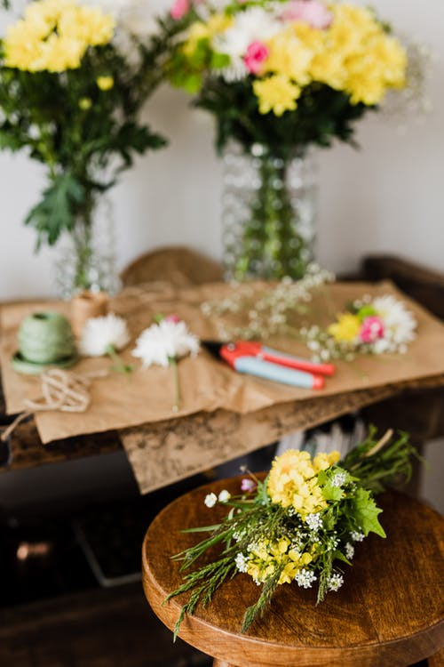 Bouquet of flowers on wooden stool near florists table