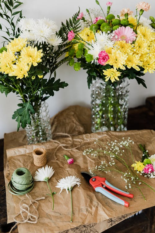 Pruner and twine rolls on table with flower bouquets