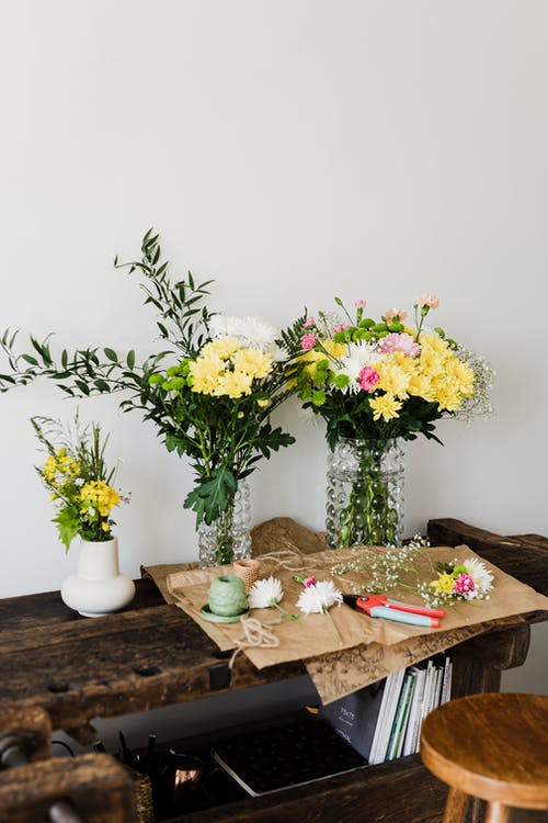 Chrysanthemum bouquets on wooden table in florist workshop