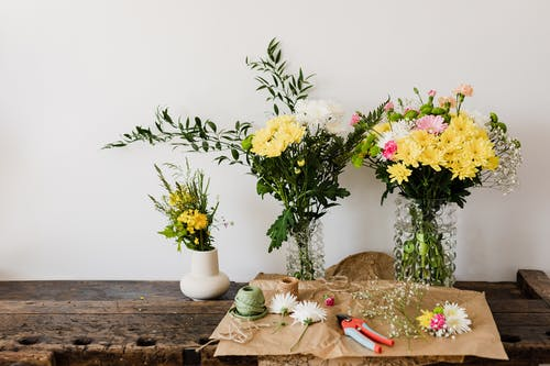 Vases with chrysanthemums on wooden table florists tools