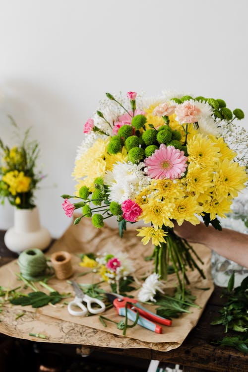 Crop unrecognizable florist composing chrysanthemum bouquet in workshop near messy table covered with cut leaves and floristry tools