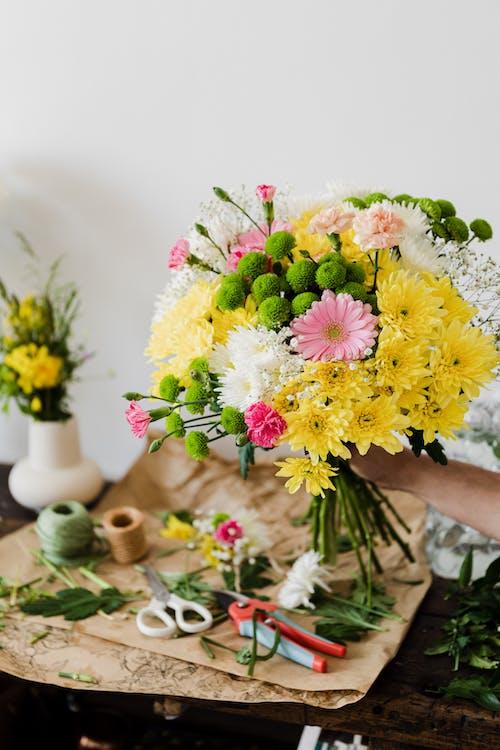Crop florist arranging flowers in shop