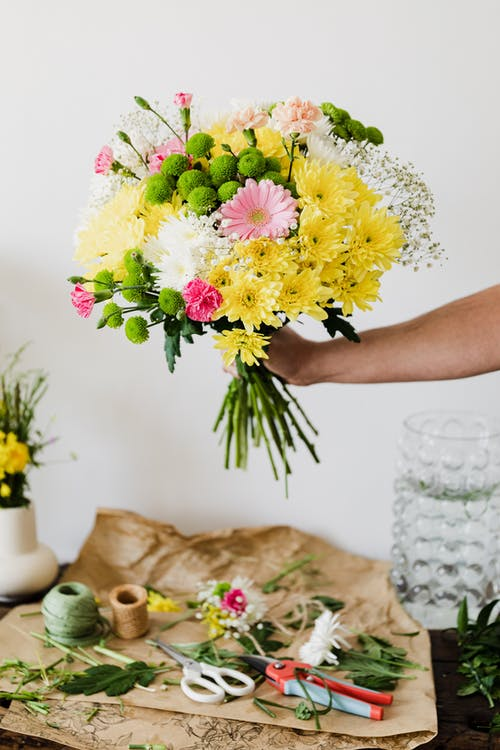 Crop faceless florist composing chrysanthemum bouquet in florist workshop at messy table covered with scattered leaves and bits of stems