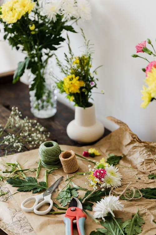 Scissors and pruner together with twine rolls among cut leaves and flowers on wooden table with vase bouquets in floristry workshop