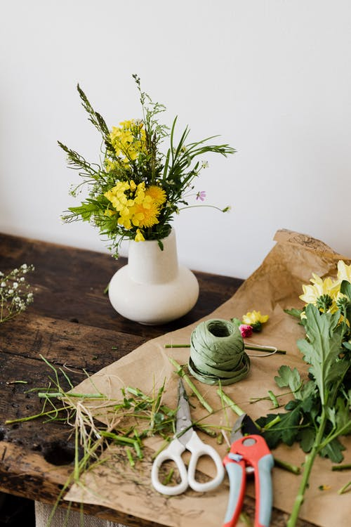 From above of tender yellow flowers in white ceramic vase placed on messy wooden table covered in cut leaves with scissors and pruner