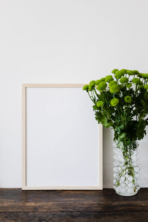 Empty mockup picture in wooden frame and bouquet of green chrysanthemums in stylish glass vase on dark brown wooden table
