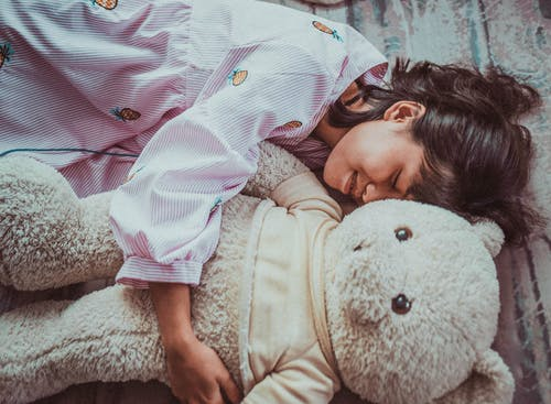 Girl in White and Pink Floral Robe Lying on White Bear Plush Toy