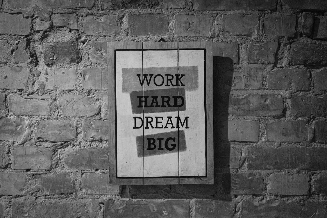Black and white frame with inspirational Work Hard Dream Big inscription hanging on brick wall