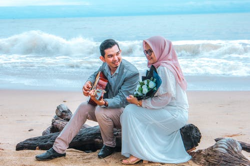 Happy Asian man smiling and playing guitar for woman in hijab while sitting on log during romantic date on beach near waving sea