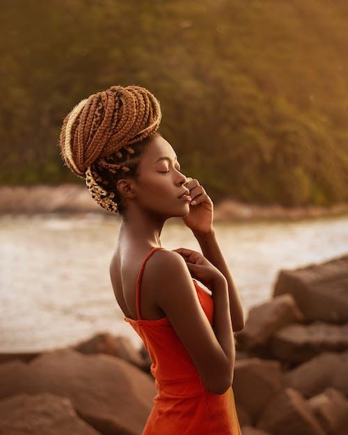 Stylish black woman touching face near water