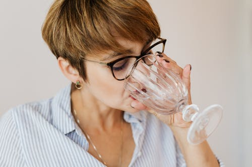 Crop serious female with short hair in shirt with stripes and glasses drinking water while sitting in creative workplace