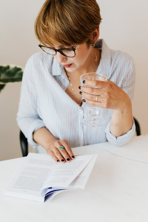 Content woman with glass of water reading book