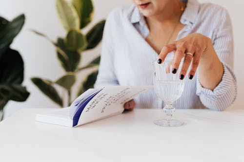 Woman with glass of water reading book