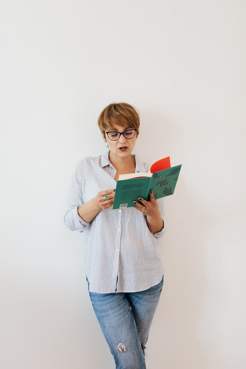 Serious woman with short hair in glasses and jeans with shirt in stripes standing near white wall and reading book
