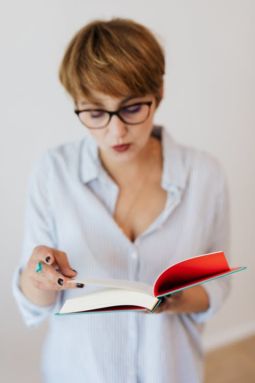 Focused woman reading interesting book in hardcover