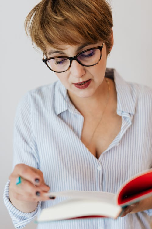 Crop positive woman with interesting book