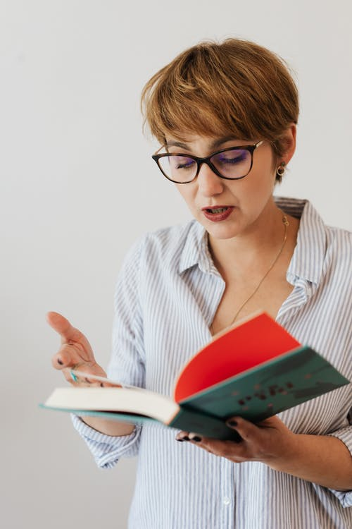 Clever woman in eyeglasses reading book
