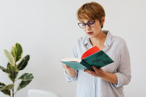 Smart woman in eyeglasses reading book