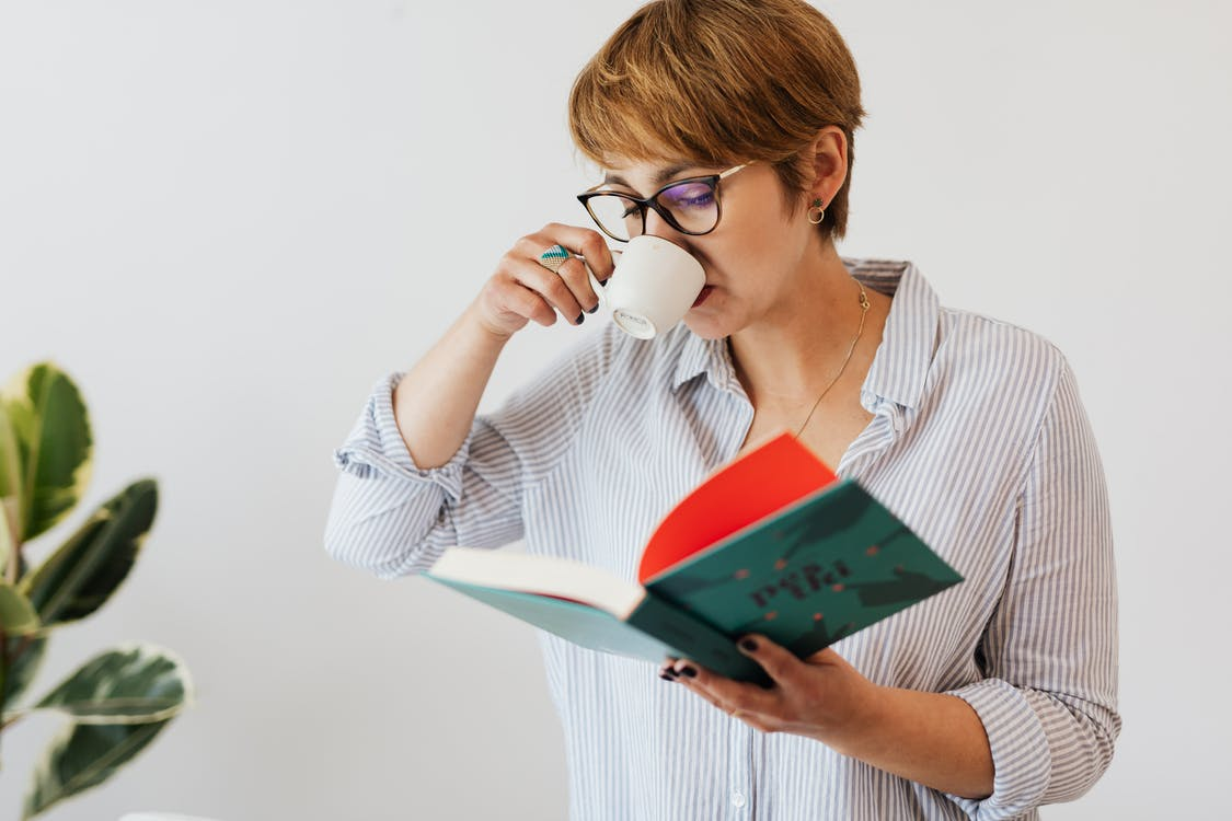 Crop pensive female in eyeglasses and casual wear reading interesting book in hardcover and drinking hit aromatic coffee from white ceramic cup against white wall and green plant