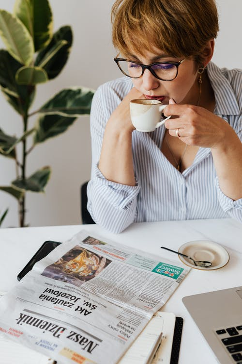 Focused woman drinking coffee and reading newspaper