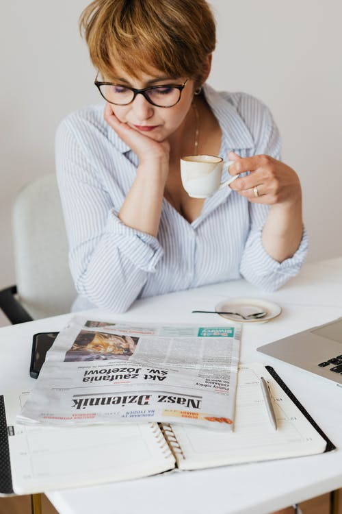 Focused woman drinking coffee and reading daily newspaper article