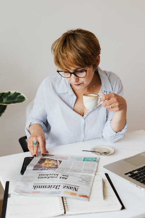 Serious woman with cup of coffee reading newspaper
