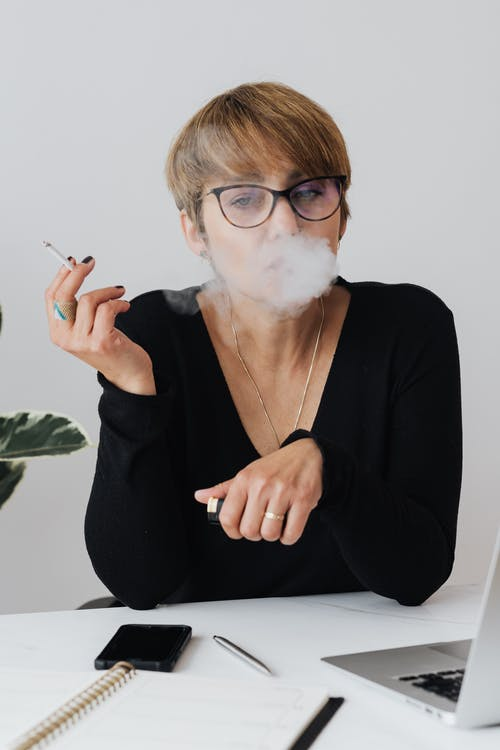 Thoughtful businesswoman smoking cigarette while sitting at table