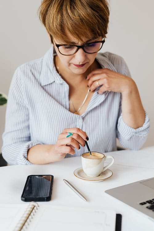 Crop serious female in eyeglasses and formal shirt sitting at table with gadgets and notebook while stirring aromatic fresh coffee