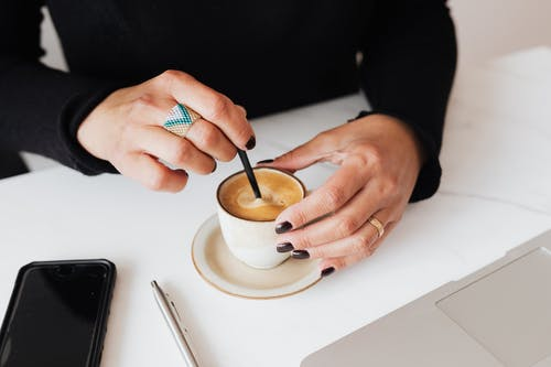 Crop woman with stylish ring stirring hot espresso