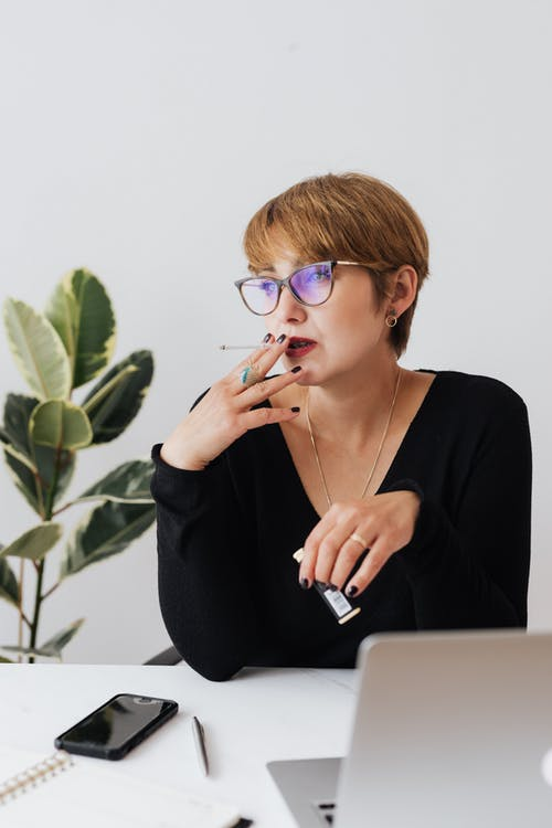 Pensive businesswoman working on laptop and smoking cigarette