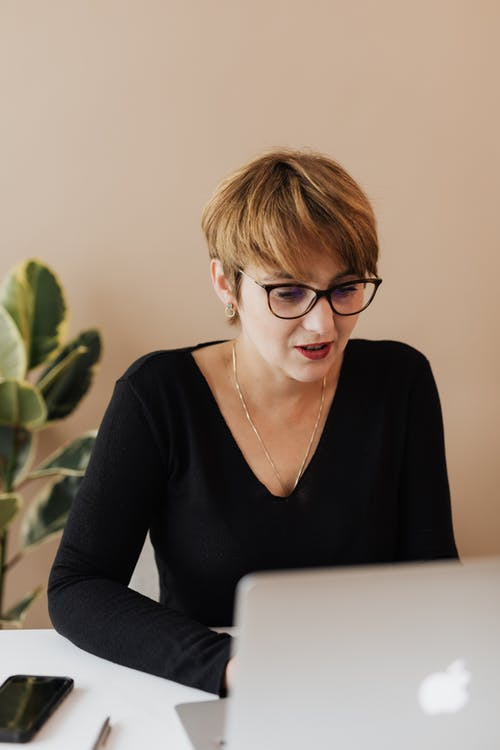Positive businesswoman working on project with laptop