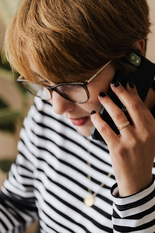 Crop short haired female entrepreneur in casual clothes and eyeglasses having phone conversation while working remotely