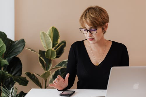Concentrated female manager in casual outfit and eyeglasses reading message on smartphone while sitting at table with laptop in cozy workspace
