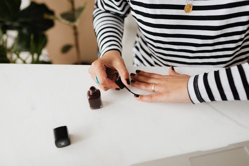 Unrecognizable female doing manicure with black nail polish on white table resting at home during weekend