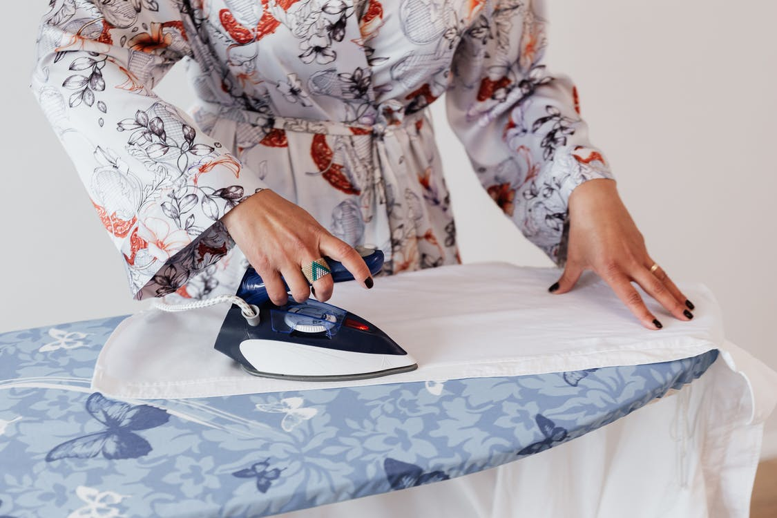 Crop faceless female in stylish silk robe ironing formal white shirt on blue ironing board by using contemporary small iron against white plain wall