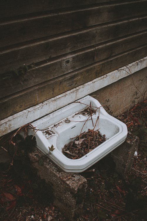 Basin with twigs outside house