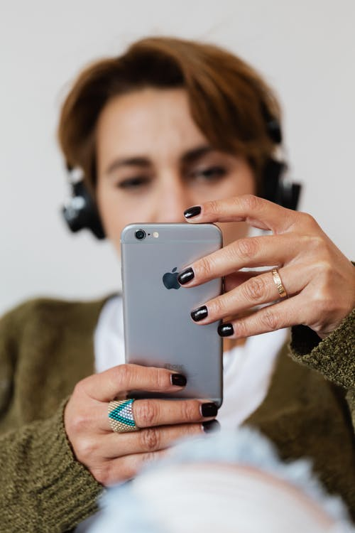 Blurred female in casual clothes wearing stylish ring surfing contemporary mobile phone and listening to music via headphones