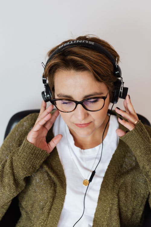 Positive woman listening to music in headphones