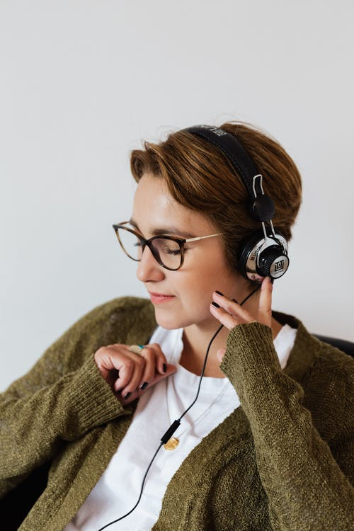 Glad woman in eyeglasses using headphones