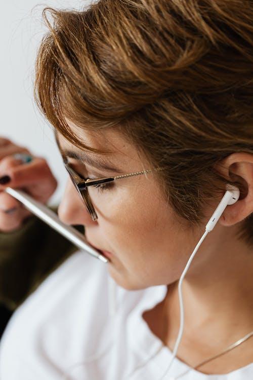 Crop pensive woman in earphones with silver pen